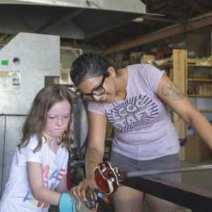Glass artist blowing a glass float with young student