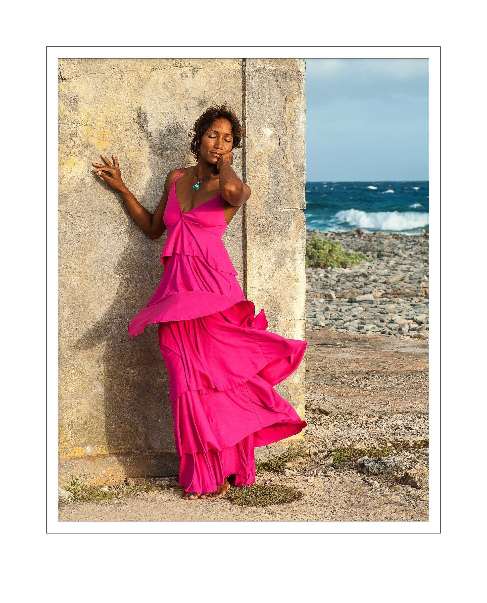 Photograph of a woman on the beach with pick dress