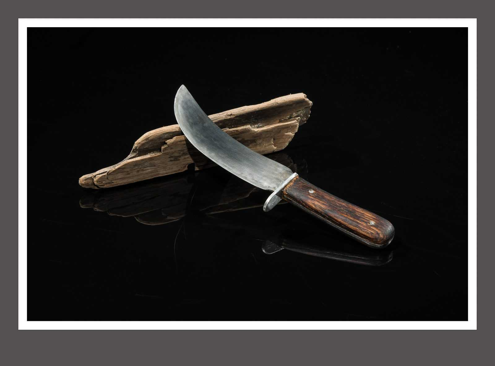 Still life photograph knife on driftwood black background